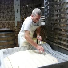 """Une fois que le caillé a été tranché et réduit en granulés, Gilles le rassemble dans un grand tissu en lin et l'insère dans le presse-tome. Le presse-tome rassemble non seulement les granulés, mais essore en quelque sorte la tome afin d'éliminer le maximum de lactosérum """"petit lait"""". L'opération est répétée 2 ou 3 fois."""