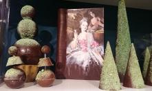 """Carnet de Marie-Antoinette en chocolat, entouré de petits bosquets et sapins taillés à la mode des """"jardins à la française"""" par le jardinier André Le Nôtre."""