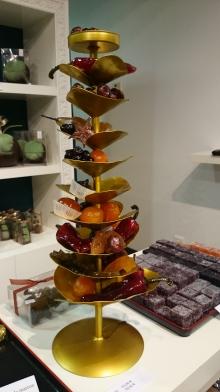 Plateau de fruits confits et pâte de fruits délicieusement goûteuses et scintillantes. On dirait une cascade infinie de fruits, comme une corne d'abondance ouverte en pleine boutique.